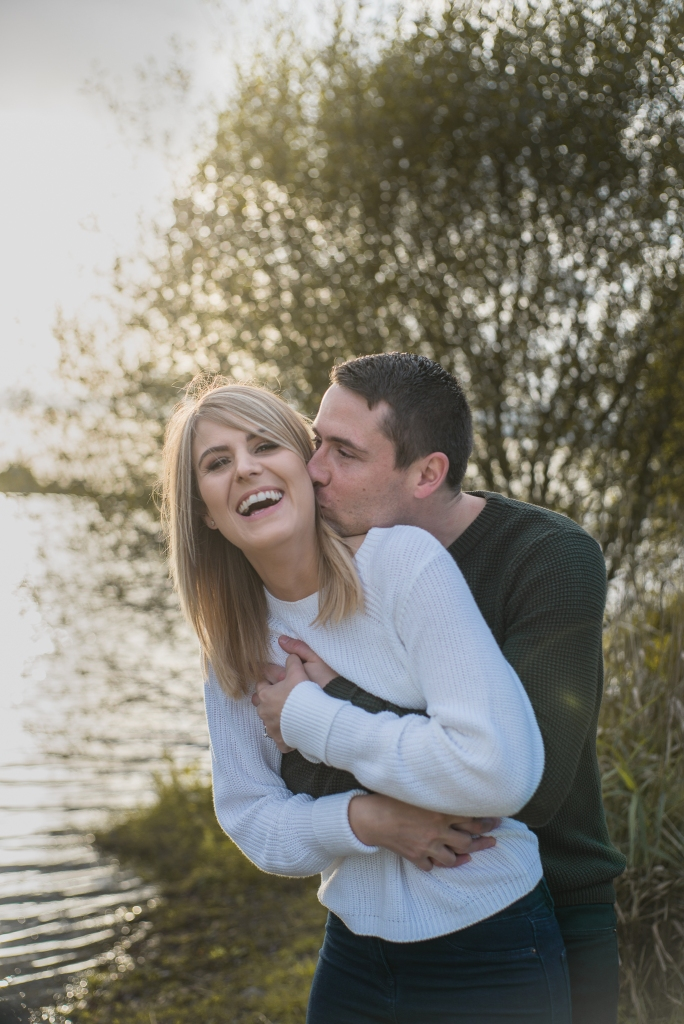 A young, casually dressed couple embrace by the side of a lake. The young man embraces his fiancée from behind, while kissing her neck. The young woman laughs.