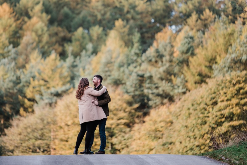 A young, engaged couple wearing winter coats are dancing on the brow of a wide path in a forest. The trees in the background are a blend of greens and yellows.